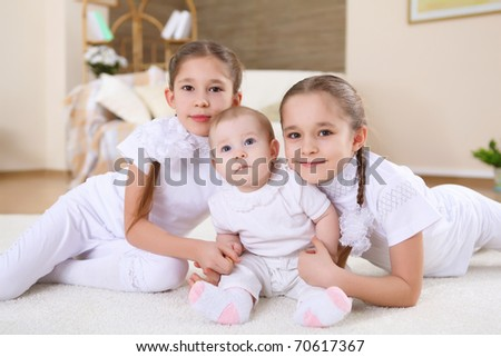 two twin sisters at home together laying at the floor