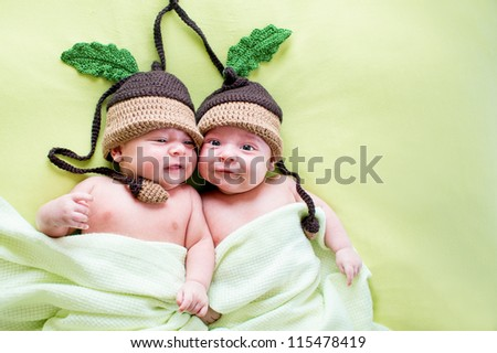 two twins brothers babies weared in acorn hats - stock photo