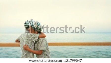 two twins on the quay in the sea hold each other in  brothers friendly embrace in the evening