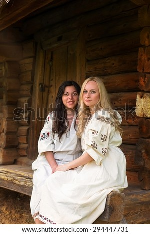 Two ukrainian girls in national costumes at the old wooden house porch - stock photo