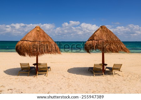 Two Umbrellas and chairs on sand beach - stock photo