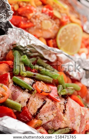 Two uncooked chicken breast dishes in foil trays - stock photo