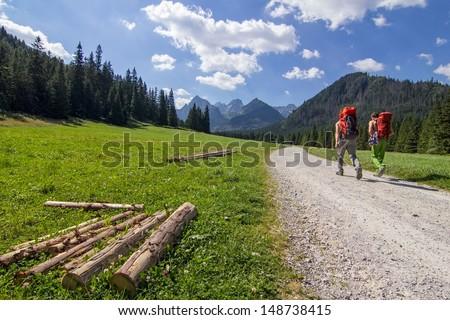 Two unidentified men walk the path to the mountains - stock photo