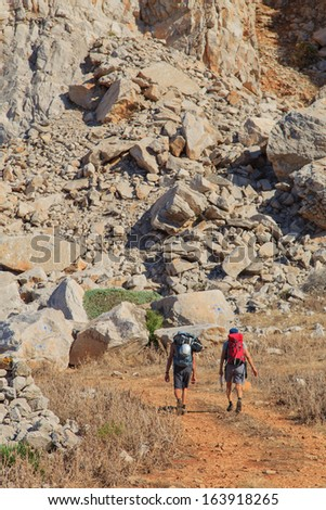 Two unidentified men walk the path to the rocks in Sicily, Italy - stock photo