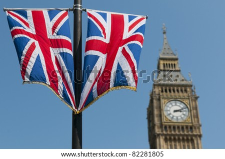 Two Union Flags flying in front of the clock tower, commonly referred to as Big Ben, of the Palace of Westminster.
