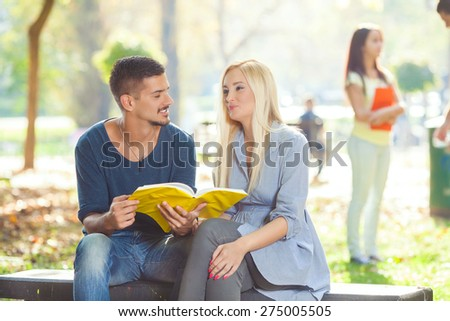 Two university students sitting in a park preparing exam together - stock photo