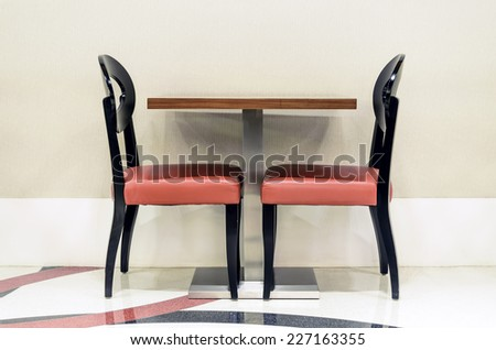 Two unoccupied red restaurant chairs by the wall - stock photo