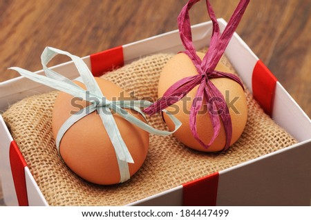 Two unpainted eggs with bows in a box