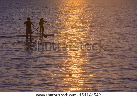Two unrecognizable paddle surfers with crossing paddles in silhouette at sunset. - stock photo