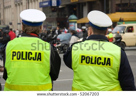 Two unrecognizable polish police officers on a street - stock photo