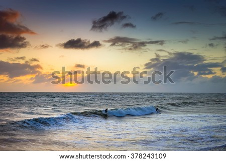 Two unrecognizable surfers riding the waves at sunset near Brighton Beach, South Australia