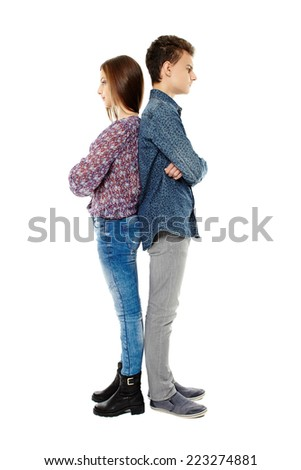 Two upset teenagers standing back to back isolated on white background