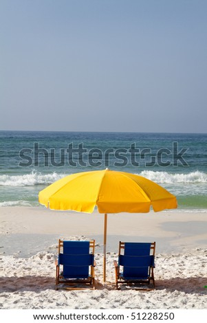 Two vacant beach chairs shaded by an umbrella are set up on the beach. - stock photo