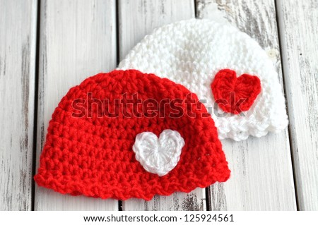 Two Valentines day crochet baby hats with hearts - stock photo