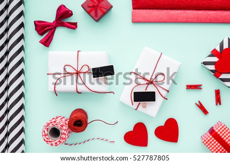 Two Valentines gifts packed in white paper with red bows and small chalkboards. View from above. Flat lay.