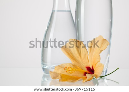 Two vases with clean water and hibiscus flower on a glass table - stock photo