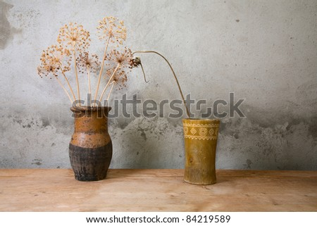 Two vases with dry colours on a wooden table - stock photo