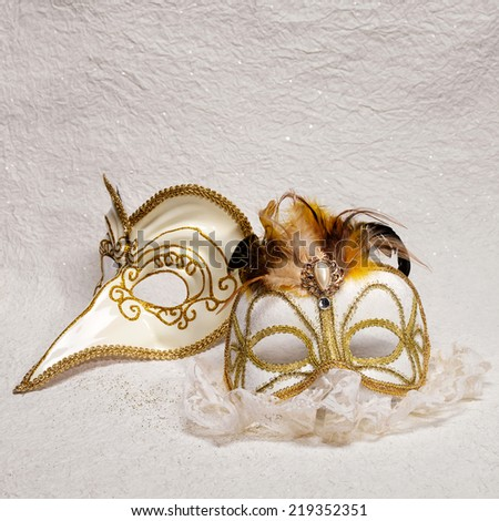 Two Venetian carnival masks decorated with feathers and pearls
