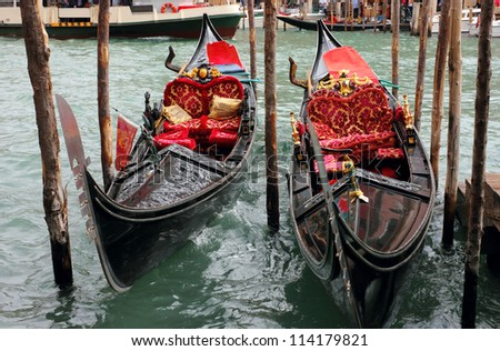 Two Venetian Gondolas, docked near the Rialto Bridge on Grand canal in Venice.