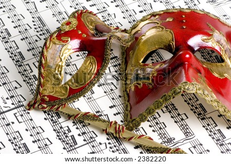 Two venetian masks lay on top of an old score of music