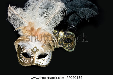 Two venetian masks lying on black background