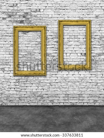 Two vertical golden frames on white brick wall - stock photo