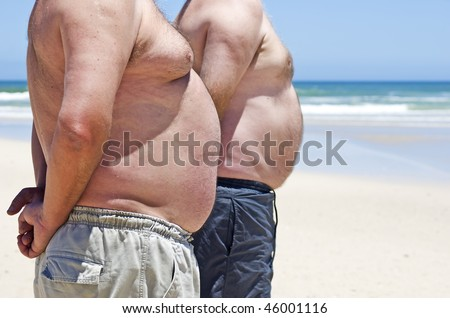 Two very fat men on the beach - stock photo