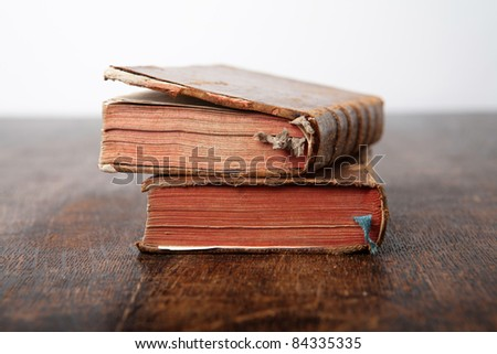 two very old books lying on old wooden table - shallow depth of field - stock photo