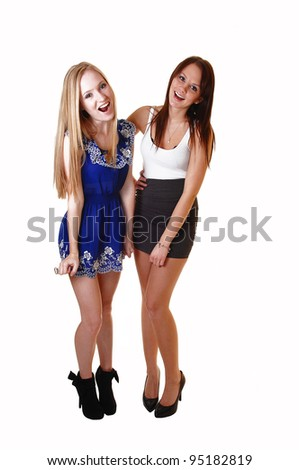 Two very pretty woman standing in the studio having fun and laughing in dresses and high heels, one blond and one brunette, over white. - stock photo