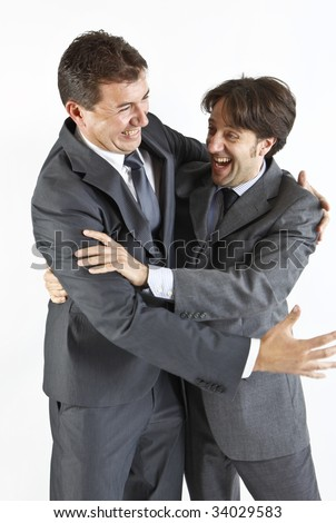 two  victorious businessmen hugging