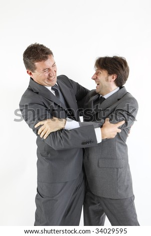 two  victorious businessmen hugging - stock photo