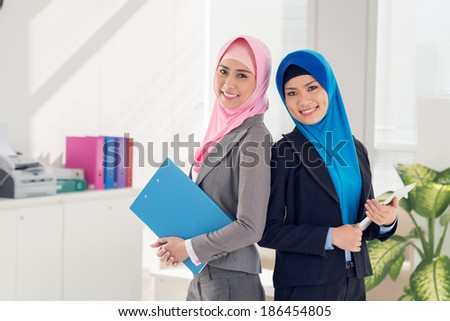 Two Vietnamese business ladies standing with documents in the office - stock photo