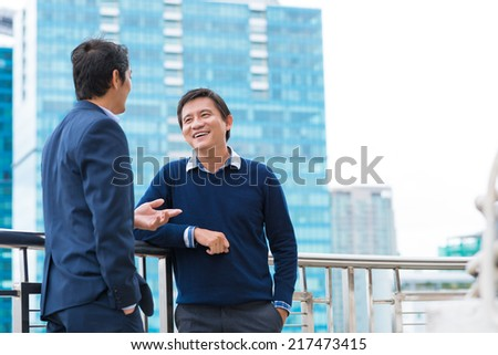 Two Vietnamese male coworkers talking and smiling - stock photo