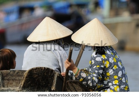 Two Vietnamese Seen at a Morning Floating Market in Vietnam. - stock photo
