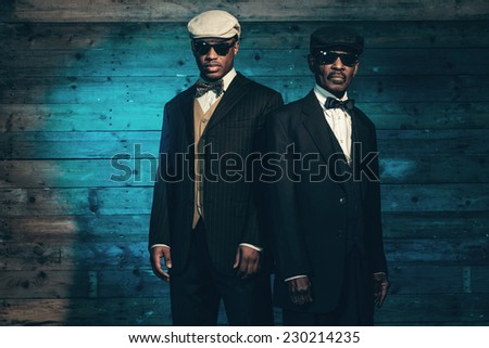 Two vintage african american gangsters in front of old wooden wall. Wearing black sunglasses with suit and cap. - stock photo
