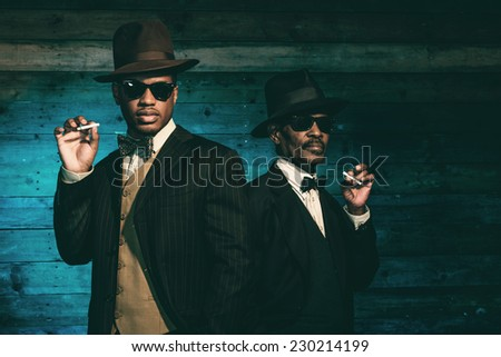 Two vintage african american gangsters smoking cigarette in front of old wooden wall. Wearing black sunglasses with suit and hat. - stock photo