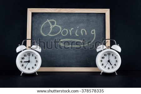 "Two vintage alarm clocks showing 9 and 5 o'clock with the word ""boring"" handwritten on chalkboard on black background. Nine to five corporate working hours concept."
