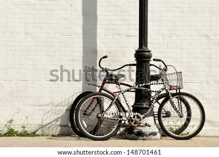 Two vintage bicycles locked to a lamp post against white painted brick wall. - stock photo