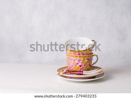 two vintage cups, sauceres and spoons on a white background - stock photo
