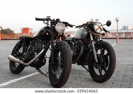 Two vintage custom caferacer motorbikes in the parking lot during sunset. Outdoors lifestyle - stock photo