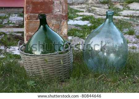 two vintage empty demijohns in a garden