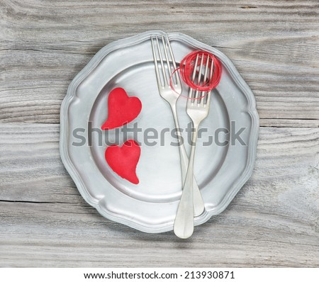 Two vintage fork and two scarlet hearts on an empty pink plate