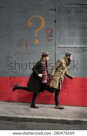 two vintage investigators are running in the street, there are question marks painted on the wall - stock photo