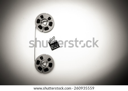 Two vintage 8mm blue reels vertically connected with film and a little clapper board isolated on white background - stock photo
