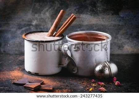 Two vintage mugs with tea and hot chocolate, served with dry tea, rose buds, chopped chocolate and cinnamon sticks over black background - stock photo