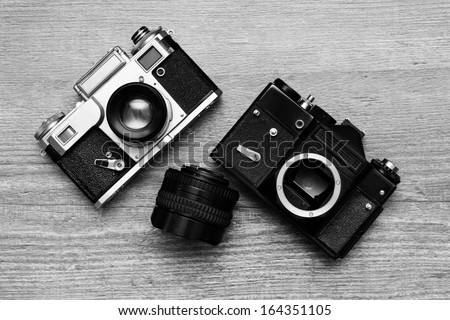 two vintage photo camera and lens on a wooden background - stock photo