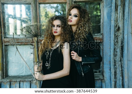 two vintage women as witches, posing beside an abandoned building on the eve of Halloween - stock photo