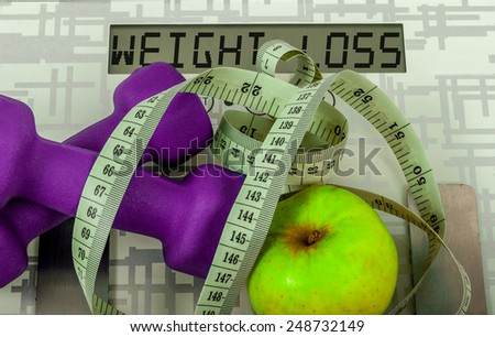 Two violet dumbbells and apple and measure tape on weighing machine with sign weight loss - stock photo