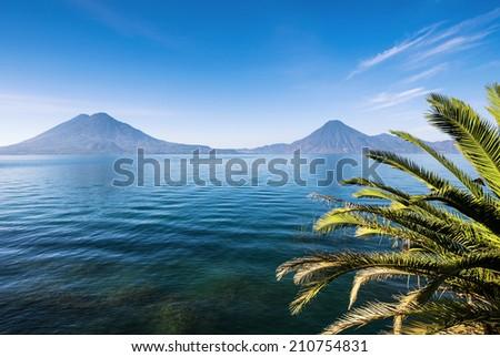 Two volcanoes on beautiful lake Atitlan in Guatemala - stock photo
