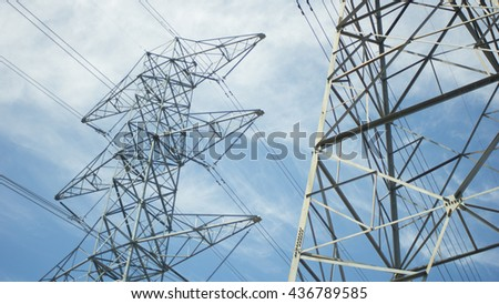 Two Voltage Power Lines with a blue sky and clouds